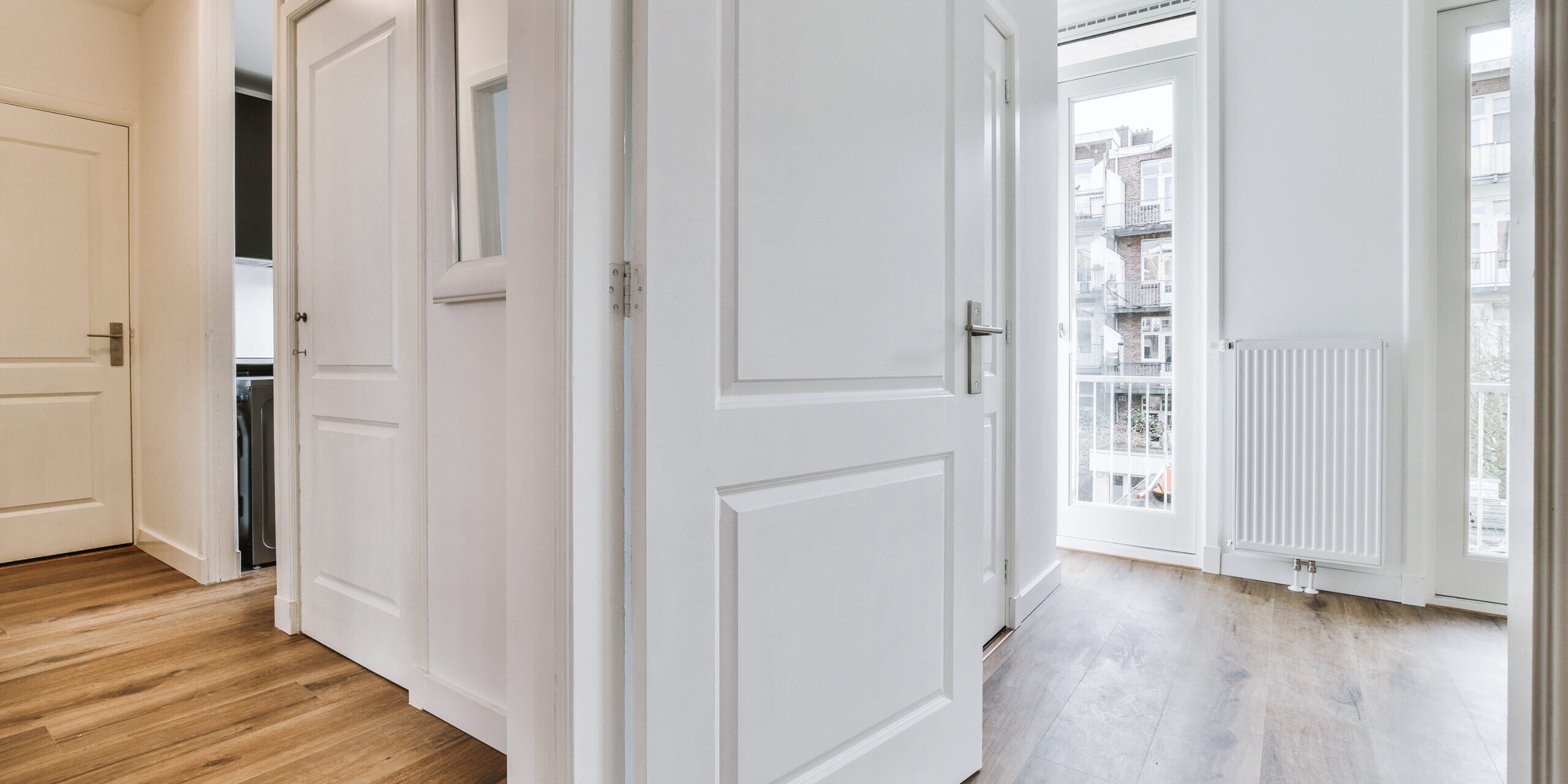 White door opened from corridor into empty room with radiator in modern apartment